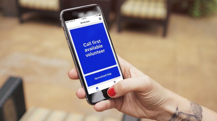 Hånd der holder en smartphone med appen 'Be my Eyes', klar til at ringe til første ledige frivillige