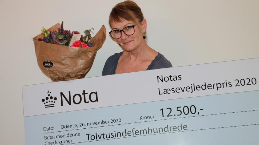 Glad kvinde med blomster og check på kr. 12.500