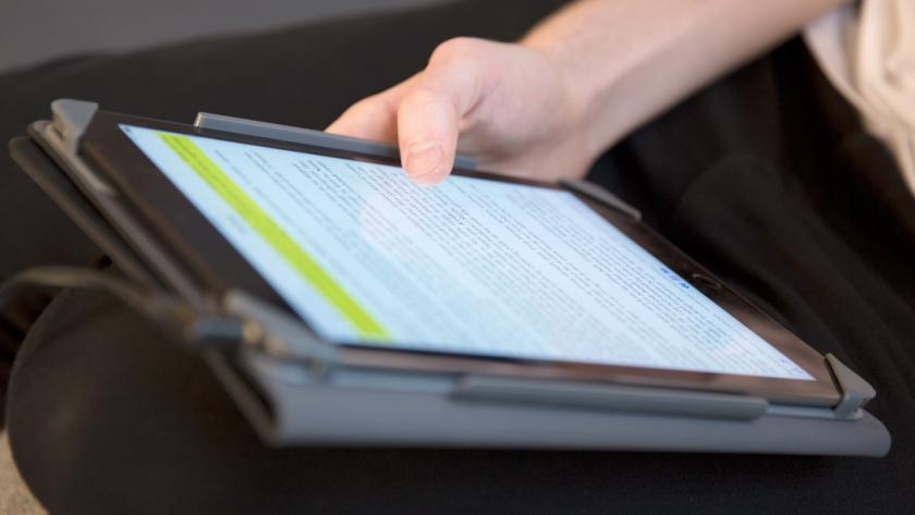 Person sidder med tablet der viser oplæsning af tekst
