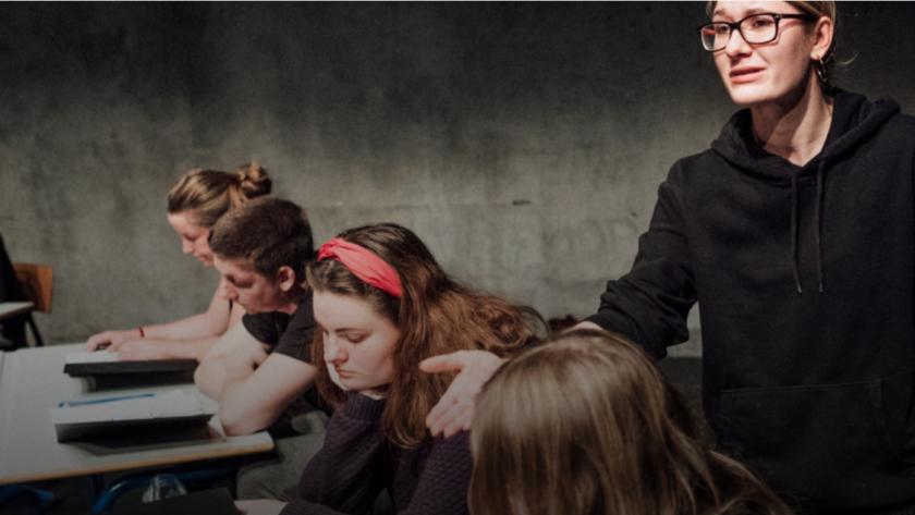 Elever siddende ved deres pulte i et klasseværelse. En lærer går imellem pultende og taler.
