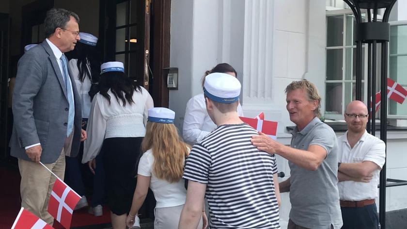 glade studenter entrerer rådhuset. mennesker smiler og har flag.
