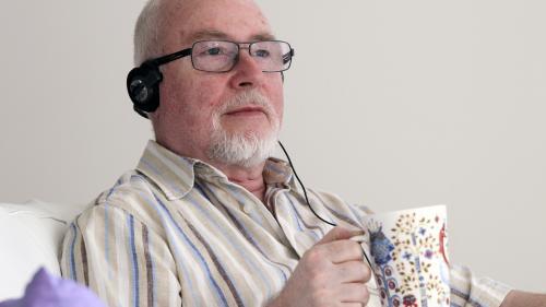 Ældre mand lytter til en lydbog