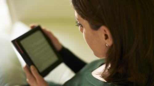 Ung kvinde læser på tablet